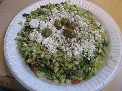 The Greek Salad is finely chopped and topped with a light olive oil/lemon dressing and a generous portion of feta cheese.