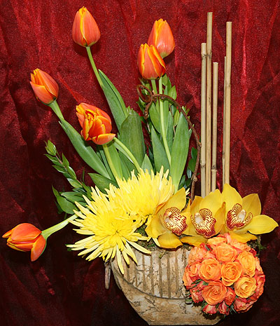 Orange tulips, Fuji mums, Cymbidium orchids and a ball of spray orange roses in a clay pot. (about $80).