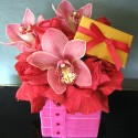 """Valentine Surprise""- Ruffled scarlet roses with pink cymbidiums and a ""hint"" of Godiva chocolate. ( in a 4x4 cube with 2 pieces of Godiva) $75."