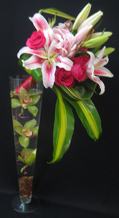 A unique arrangement of Star gazer Lilies with Hot Pink Roses bouquet style accented with Tea leaves in a tall Trumpet vase with floating Cymbidium Orchids. This arrangement stands over 3 feet Tall. $150.