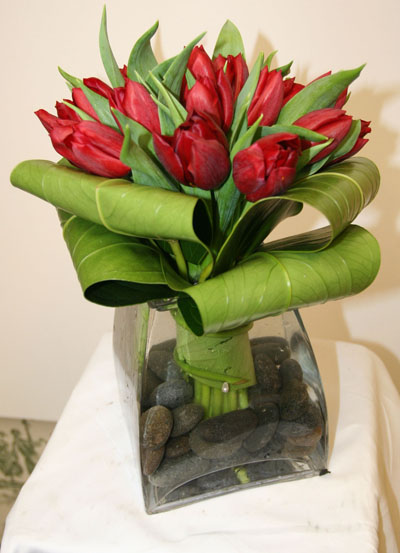 20 Red Tulips with folded tropical leaves set in a tapered vase. Cost is $75. This arrangement can be order at the store for local delivery.