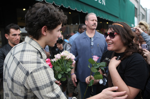 Nick Jonas giving roses to a fan.