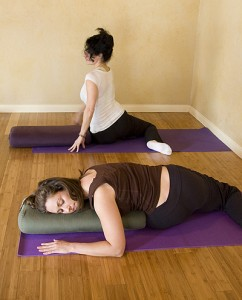 Demonstrating how to properly enter this restorative pose, Claire (in white shirt) twists her torso toward the front before folding over the bolster.