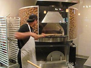 You can watch the pizzas go in and out of the oven.